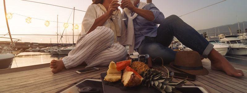 riche Senior couple toasting champagne on sailboat vacation - Happy ma